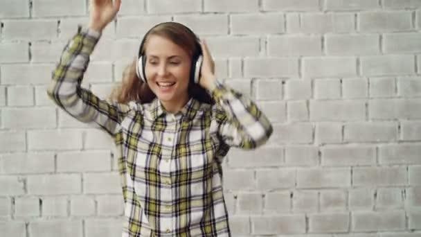 Portrét veselá mladá dáma, tance a zpěvu, poslechu rádia v bezdrátové sluchátka nosit módní ženské košile. Moderní technologie, kultura a lidé koncepce