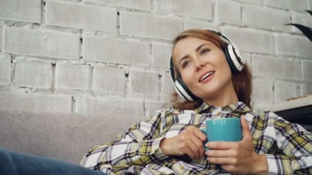 Nyugodt lány diák fárasztó a fejhallgató, zenét hallgat, éneklés és a gazdaság csésze kávé ül a kanapén, loft stílusú lakás. Kultúra, a relaxáció és az ital koncepció.