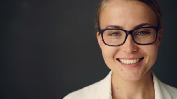 Detail zpomalené portrét veselá podnikatelka v brýlích pohledu kamery se zubatými úsměv tmavě šedém pozadí. Koncept lidi, pozitivity a emoce
