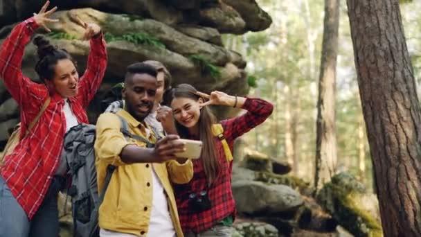 Šťastný, že turista Američan Afričana muž bere selfie s přáteli v lese poblíž obrovské skály pomocí smartphone, lidé dělají ksichty a gesta rukou zobrazeno.