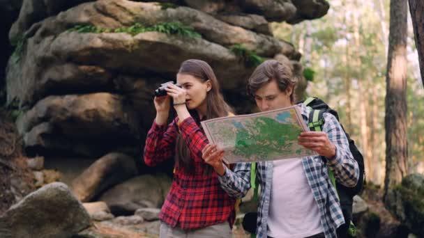 Veselý pár stojí v lese, člověk studuje mapu, dívka dívá dalekohledem pak zobrazující zajímavé místo své přítelkyni a směje.