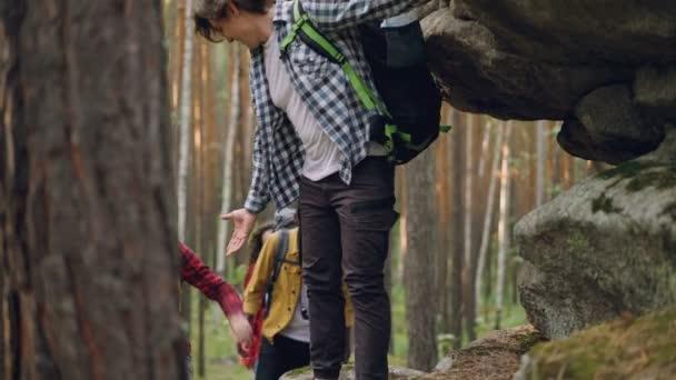 Mnohonárodnostní skupiny cestujících je trekking do obrovské skály v lese nošení těžké batohy, muži pomáhají ženám. Přátelství, dobrodružství a mládež koncepce