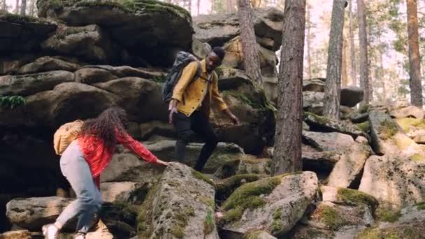 Mladý pár mnohonárodnostní je turistika, lezení po horách, americký muž pomáhá žena dává jí ruku a vytáhl ji, lidé drží batohy