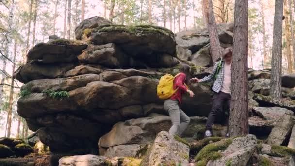 Nadšený turisté jdou horu pomáhat si navzájem, pak stojí na vrcholu a výhledem. Mladí lidé jsou nošení batohů a nosí ležérní oblečení
