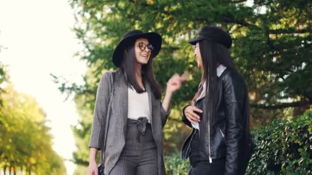 Happy girls are chatting and laughing standing outdoors on sidewalk holding bright shopping bags discussing day in mall. Women are wearing stylish clothing and glasses.
