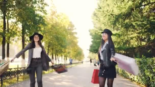 Dolly záběr přátel šťastné ženy běh a chůzi po ulici s papírové sáčky soustružení a směje se s zábavné využití volného času. Koncept nakupování a přátelství