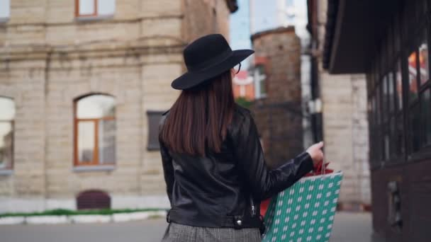 Slow motion portrait of happy young lady with long dark hair wearing glasses and hat walking with shopping bags then turning and looking at camera with glad smile.