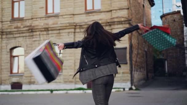 Lassított spinning az utcán gazdaság papír ajándék táskák és látszó-on fényképezőgép-boldog mosollyal izgatott fiatal nő portréja. Bevásárló- és pozitív érzelmek fogalma.