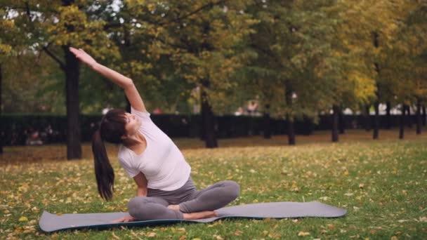 Krásná dívka je soustředěna na praxi jógy sedí na rohoži v parku v lotosové pozici a ohýbání do stran kypřicími rameno. Zdravý životní styl a rekreace koncept.