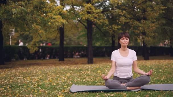 Attraktive junge Dame sitzt in Lotus-Position auf Yoga-Matte im Park halten Hände in Mudra auf Knien und atmen entspannend nach dem Training. Meditations- und Naturkonzept.