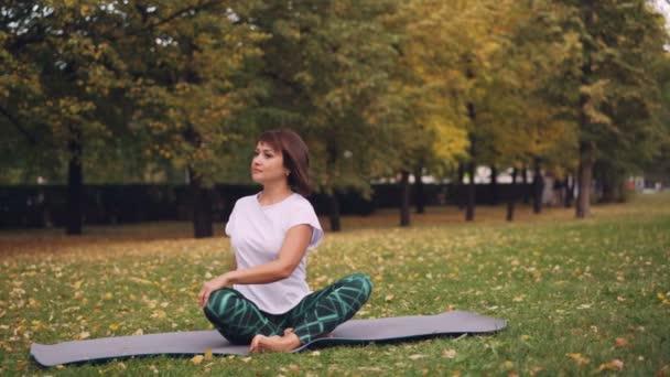 Flexibilní dívka yogini procvičuje simple twist pozice pak odpočívá v lotosové pozici sedí na jógu na trávě v parku. Rekreační oblast a lidé koncept