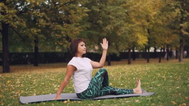 Krásná dívka v sportswear je cvičení v parku praktikujících sedící zvraty a vpřed ohyby na jógu na teplý podzimní den. Příroda, sport a zdravotnictví koncepce.