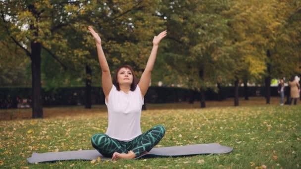 gut aussehendes Mädchen legt Hände in namaste, sitzt in Lotusposition und atmet entspannt ihren Körper und Geist. Meditation, Hatha Yoga und People Konzept.