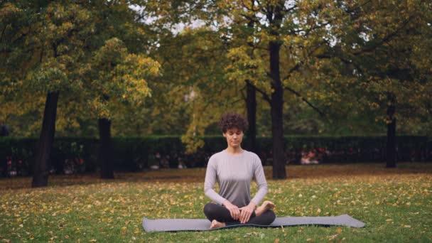 Flexibilní mladá dáma sedí na rohoži v józe pozice užívat čerstvý vzduch, klid a odpočinek. Zdravý životní styl pro městské lidi, aktivní mládež a koncepce přírody.