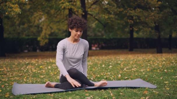 Štíhlá mladá dáma dělá pořadí ásany jóga sedí na podložce v parku na podzimní den s krásnou trávou a stromy kolem sebe sám. Rekreace a sport koncept.