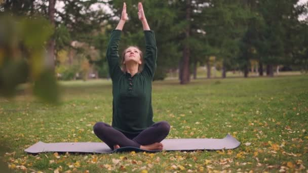 Good-looking girl is sitting in lotus position on yoga mat on grass in city park holding hands in namaste then in mudra on knees and breathing. Meditation and nature concept.
