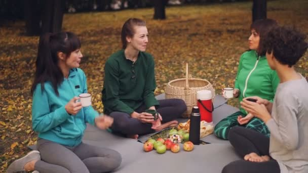 Beautiful sportswomen are relaxing after outdoor training having picnic on mats eating snacks and drinking tea. Girls are talking and laughing enjoying nature.