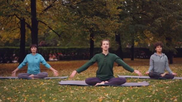 Spirituelle junge Frauen meditieren im Lotussitz auf Yogamatten im Park und atmen nach dem Outdoor-Training entspannt frische Luft. Meditation und Naturkonzept.