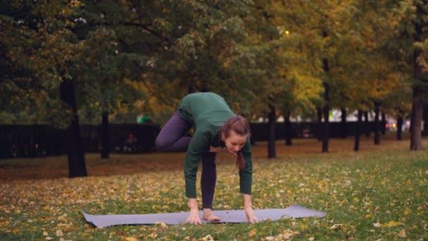Flexibilní mladá žena je balancování na jedné noze, drželi se za ruce v namaste těší individuální praxe v parku. Krásná podzimní příroda je v pozadí.