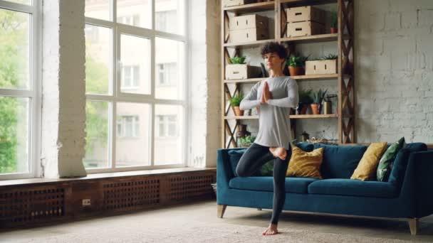 Krásná mladá dáma v sportswear procvičuje vyrovnávání ásany doma dělá jógu samostatně stojící na jedné noze zaměřené na rovnováhu. Mládež, aktivní životní styl a hobby koncepce