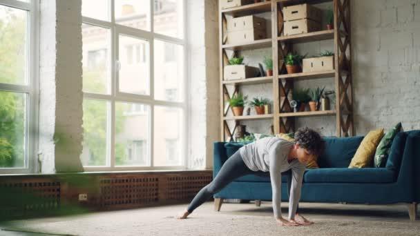 Flexibilní mladá žena je cvičení doma cvičení jógy ásany na patře moderní byt, protažení těla, rukou a nohou. Koncept mládí a zdraví