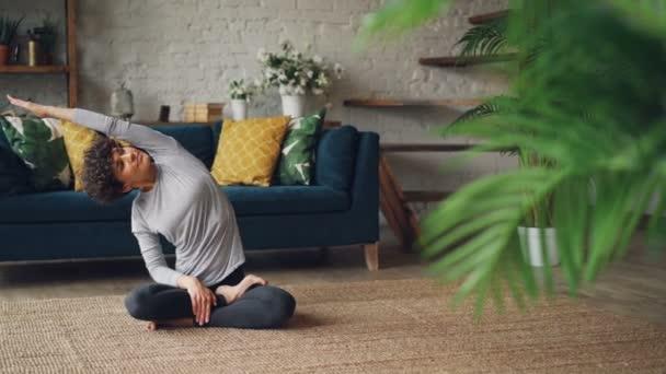 Štíhlá dívka kudrnaté vlasy je dělá jógu doma v sedící poloze pak odpočívá v lotosu představují užívat si klid a pohodlí. Mladí lidé, meditace a zdraví koncepce.