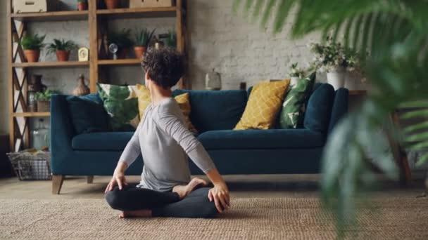 Atraktivní mladá dáma je relaxace v lotosu představují po tréninku sedí na podlaze koberec a dýchání. Koncentrace, meditace a mládež koncept životního stylu