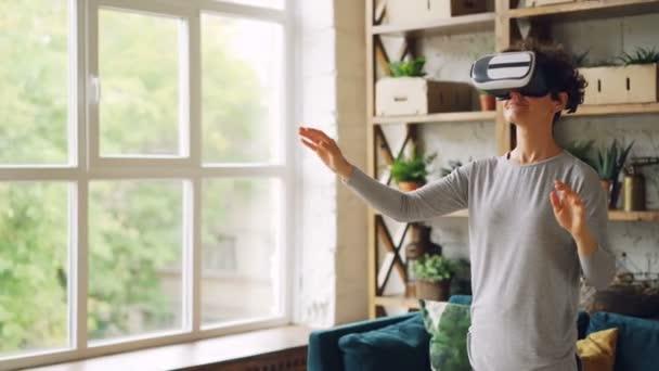 Šťastná mladá dáma má na sobě moderní umělé reality brýle stojí doma v podkroví apartmány a ukázal. Kudrnaté vlasy dívka má na sobě běžné oblečení