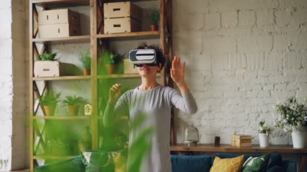 Slender girl is using virtual reality glasses at home standing in loft style room and moving hands playing game. Modern technology, leisure and new experience concept.