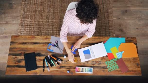 Draufsicht des lockenköpfigen Mädchens, das aus Spritzpapier ein Design entwirft, das Figuren im Notizbuch zeigt, die dann mit Klebstoff aufgeklebt werden. Arbeits- und Vorstellungskonzept.