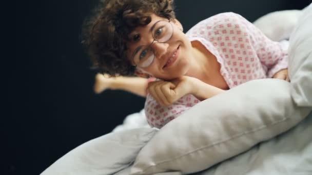 Portrét krásné dámy s tmavými kudrnatými vlasy v brýlích a ležérní oblečení válí v posteli s úsměvem rád a při pohledu na fotoaparát. Ložnici, pozitivní emoce a koncepce mládeže