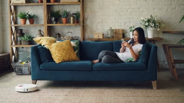 Strange Attractive Asian Girl Is Enjoying Modern Technology Using Smartphone And Robotic Vacuum Cleaner Sitting On Sofa At Home Innovations And Interiors Concept Creativecarmelina Interior Chair Design Creativecarmelinacom