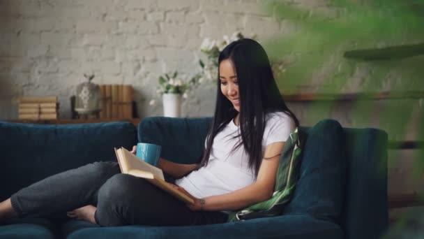 Gyönyörű ázsiai nő az olvasó könyv élvezi vicces történet, és nevetve hangulatos loft stílusú lakás a kanapén ül és pihenés. Kerti bútorok és növények