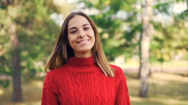 Slow motion portrait of beautiful young woman in bright red sweater standing in the park with happy smile and looking at camera. Nature and youth concept.