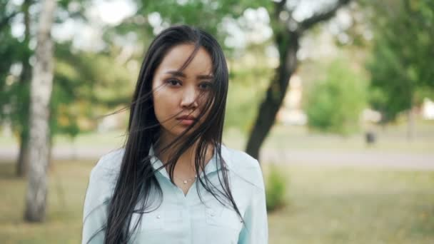 Slow motion portrait of pretty Asian woman with dark eyes and black hair wearing trendy shirt standing outdoors, smiling and looking at camera. Urban people and nature concept.