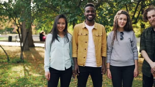 Slow motion portrait of multiracial group of students girls and guys standing outdoors together and looking at camera with happy smile. Nature and friendship concept.