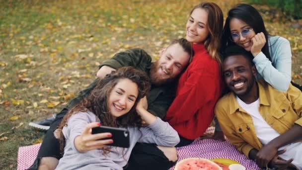 Pomalý pohyb z krásných mladých lidí bokovky s selfie v parku leží na přehoz na trávě ukazující jazykem a rukou gesta pomocí smartphonu. Koncept přátelství a příroda.
