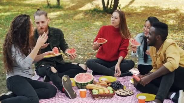 Slow motion of multi-ethnic group of men and women having picnic eating watermelon talking and laughing sitting on plaid on grass. People and nature concept.