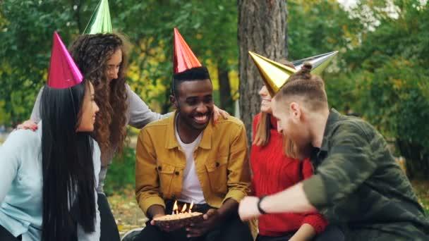 Pomalý pohyb šťastný afroamerické muže provedení si pak foukání svíčky na dort, zatímco jeho přátelé v klobouky jsou pogratuloval mu. Venkovní strana koncept.