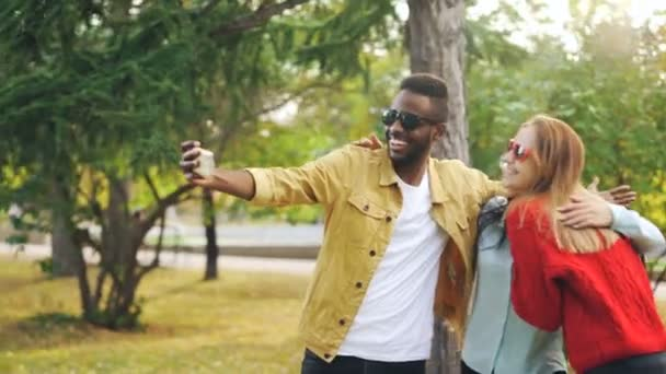 Cheerful friends multiracial group are taking selfie wearing sunglasses and hugging standing in park. Handsome African American man is holding smartphone.