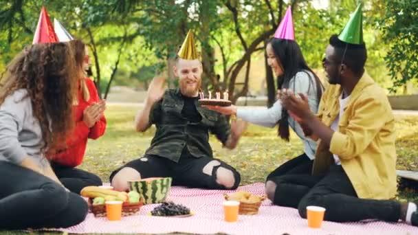 Vousatý muž slaví narozeniny s přáteli v parku foukání svíčky na dort křik a vyjadřují pozitivní emoce, zatímco přátelé jsou směje a tleská rukama