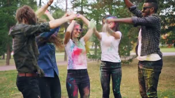 Carefree young people are having fun at Holi festival jumping, laughing and throwing colorful powder paint outdoors in park. Positive emotions and youth concept.