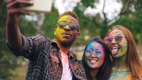 Slow motion of joyful people multiethnic group taking selfie at party with colored faces and hair. Man and women are wearing sunglasses and dirty clothing.