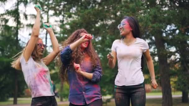 Slow motion of cheerful girls multi-ethnic group dancing then throwing paint powder at outdoor party in park. Youth culture, happy people and fun concept.