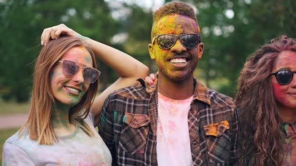 Zpomalený pohyb portrét radost mladých mužů a žen s špinavé tváře a oblečení při pohledu na fotoaparát nosit sluneční brýle a usmívá se stojící v parku