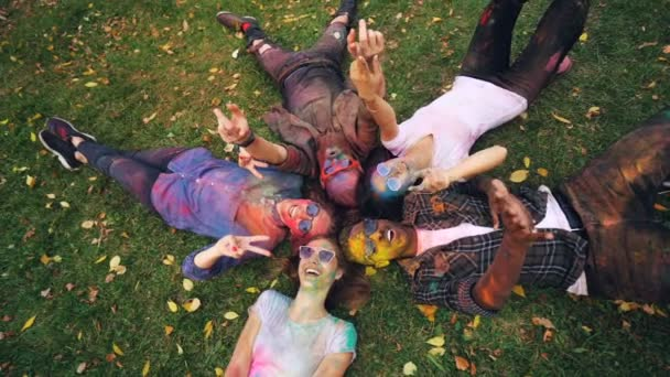Slow motion portrait of relaxed people lying on grass in park with coloured faces and clothing, looking at camera and smiling moving hands. Party and nature concept.