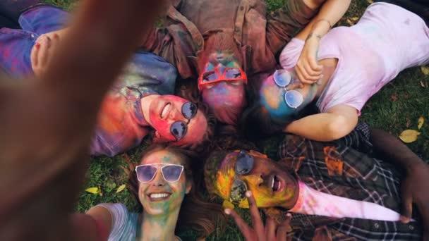 Zpomaleně snímek hlediska krásných mladých lidí s odbarvenými čelí ležet na trávě v kruhu, při pohledu na fotoaparát a pózování s gesta rukou