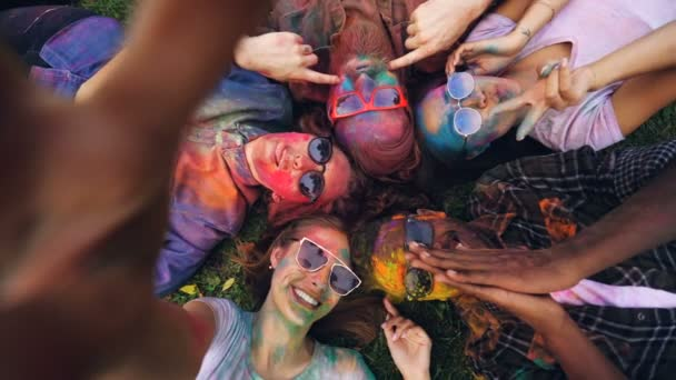 Point of view shot of happy men and women with painted faces lying on grass at Holi festival and taking selfie posing for camera. People are wearing sunglasses and dirty clothing.