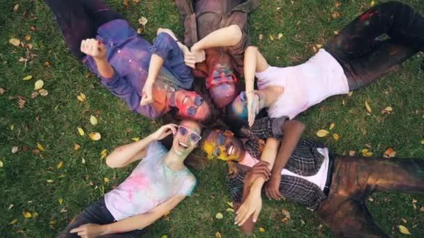 Zpomalený pohyb přiblížit uvolněnou mládeže s malovanými obličeji leží na louce a sáhl pro fotoaparát pohybu rukou a usmívá se, při pohledu na fotoaparát. Koncept zábavy a příroda