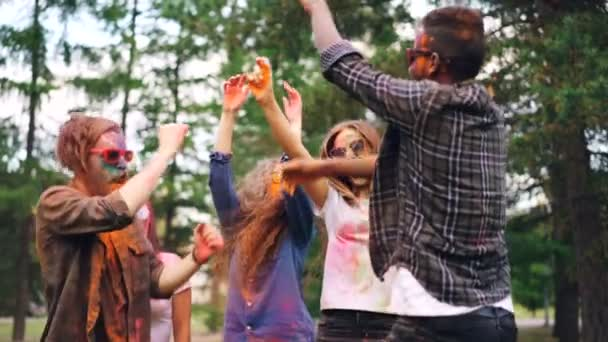 Excited girls and guys are dancing at Holi festival and throwing bright paint then laughing having fun outdoors. Holidays, millennials and nature concept.